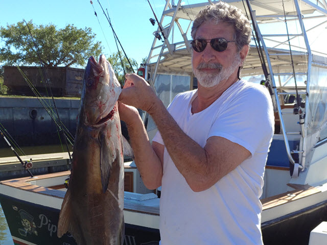 Man on boat holding Cobia fish caught off Amelia Island, FL